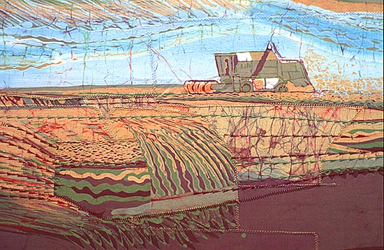 A close up version of a combine harvester surrounded by patterns of corn growing in rows and stubble. It's stitched and batiked.